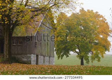 Old barn on a foggy Autumn day - stock photo