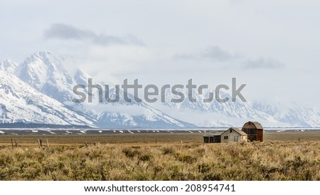 Old barn sits in front of the Grand Teton Mountains, Mormon Row Wyoming.  - stock photo