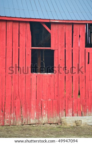 Old barn window with illusion of a hanging rope on the inside beams.