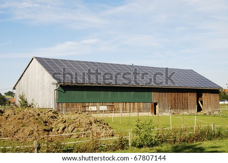 Old barn with photovoltaic on the roof - stock photo