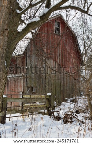 Old barn with red paint peeling, in the snows of Western New York.  - stock photo