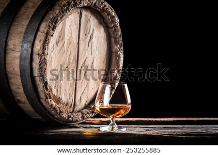 Old barrel and a glass of cognac - stock photo