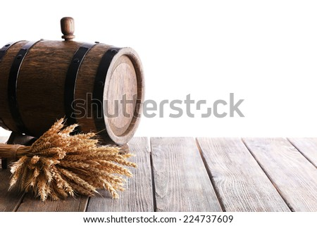Old barrel with wheat on table on white background - stock photo