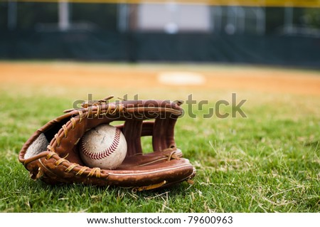 Old baseball and glove on field with base and outfield in background.