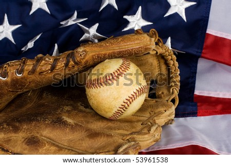 Old baseball in glove resting on American Flag. Focus is on ball. - stock photo