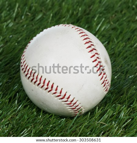 Old baseball on artificial grass.