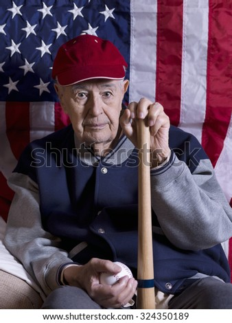 Old baseball player with bat and ball in front of an American flag - stock photo