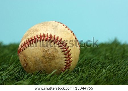 Old Baseball Sitting On A Green Field