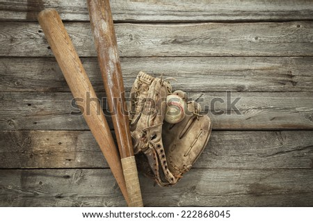 Old baseball with mitt and bats on rough wood surface - stock photo