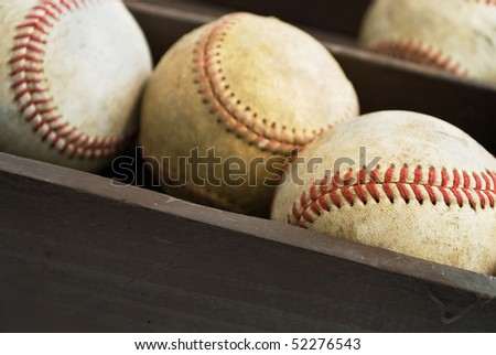 old baseballs in a wooden box, closeup on foreground ball with space for copy on side of box - stock photo