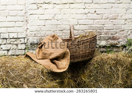 Old basket full of straw with sackcloth near vintage brick wall - stock photo