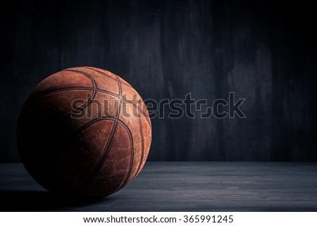 Old basketball ball on a black background - stock photo