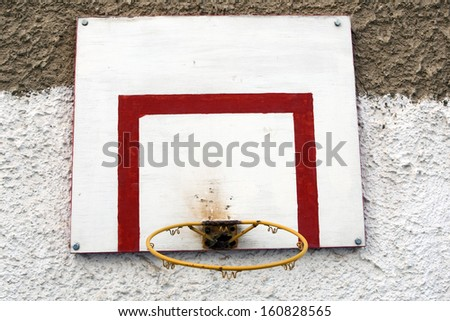 Old basketball hoop and board hanging on wall - stock photo