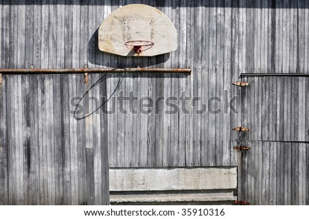 old basketball hoop on barn - stock photo