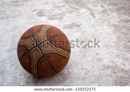 Old basketball on grunge concrete background - stock photo