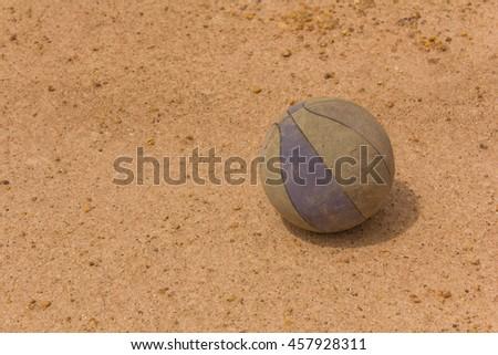 Old basketball on soil - stock photo