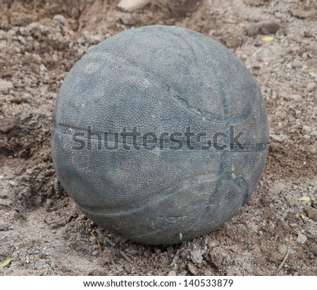 Old basketball resting on the ground. - stock photo