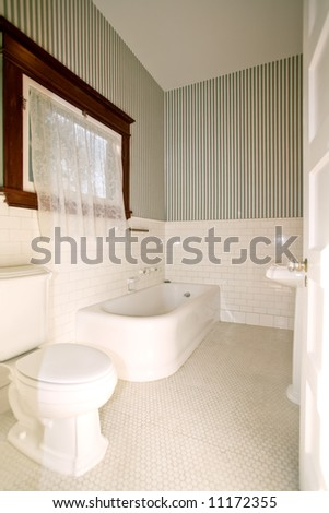 Old Bathroom with Toilet, Sink, and Bathtub - stock photo