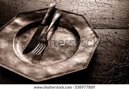 Old battered rustic pewter plate with cutlery in atmospheric shadowed light on on old cracked textured wooden surface, close up high angle view - stock photo