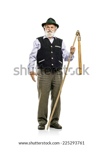 Old bearded bavarian man in hat holding flail in his hand, isolated on white background - stock photo