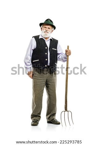 Old bearded bavarian man in hat holding pitchfork in his hand, isolated on white background - stock photo