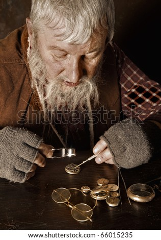 Old bearded man repairing antique watches using a magnifying glass