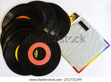 Old beat up 45s and their paper sleeves. Lots of scratches, dust and wear. Isolated on a white background. - stock photo