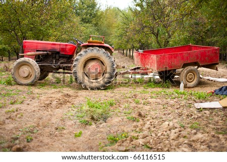 Old beaten tractor and trailer in an orchard - stock photo