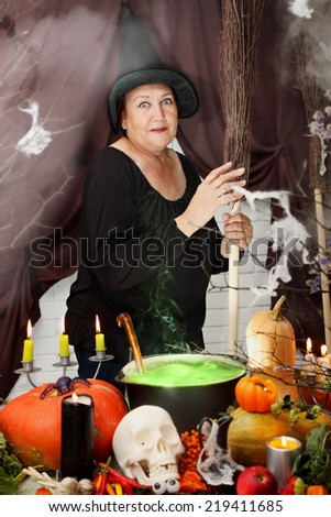 old beautiful witch  with hat and broom - stock photo