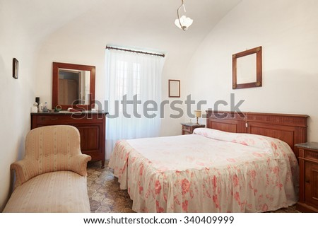 Old bedroom with queen size bed in ancient house - stock photo