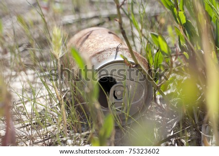 Old beer can in the wild; polution reference - stock photo