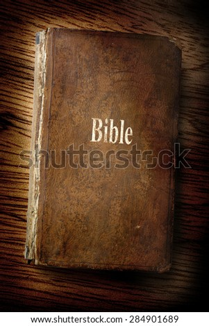 Old Bible book on the wooden background - stock photo