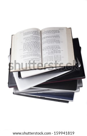 Old Bible in hebrew on top of laptop pile top view isolated on white background - stock photo
