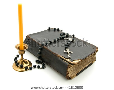 Old Bible with  candle in  bronze candlestick, cross and beads on white background - stock photo