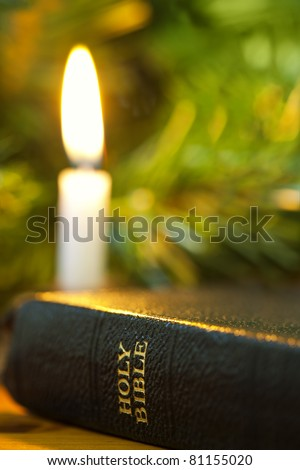 """Old Bible with Christmas candle.  Focus on words """"Holy Bible"""". - stock photo"""