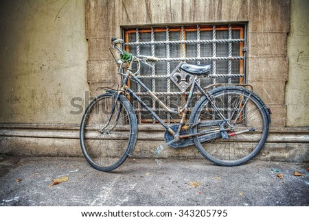 old bicycle against a rustic wall in Florence, Italy