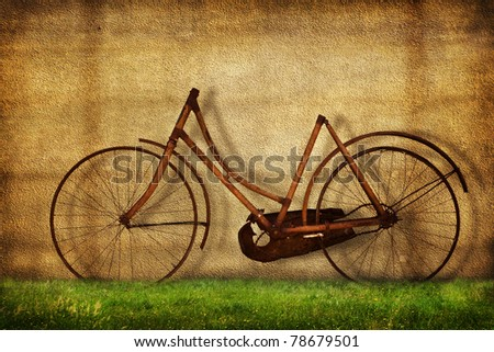 Old bicycle against wall - stock photo