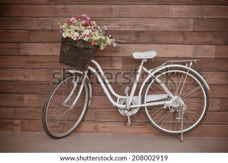 Old bicycle and flowers, vintage filter - stock photo