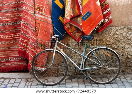 Old bicycle and traditional carpets on the street of Marrakesh, Morocco - stock photo