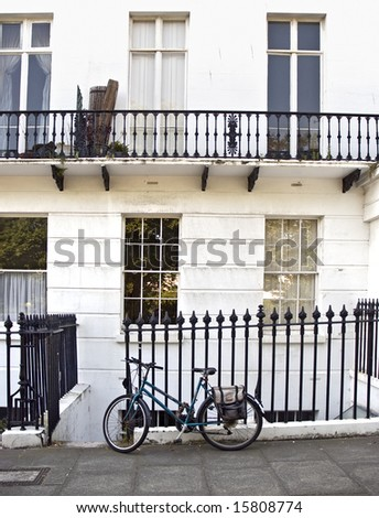 old bicycle chained to iron railings of English Regency house - stock photo