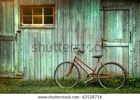 Old bicycle leaning against grungy barn - stock photo