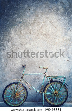Old bicycle leaning against rustic wall