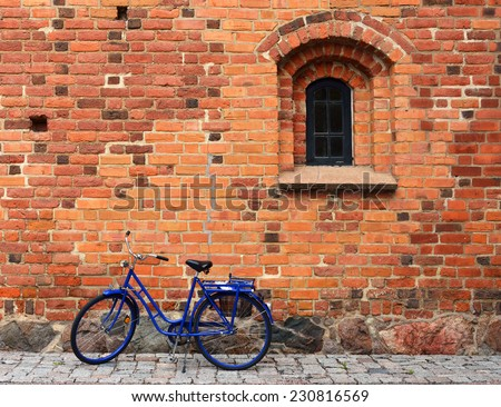 Old bicycle near red brick wall - stock photo