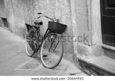 Old bicycle on street black and white - stock photo