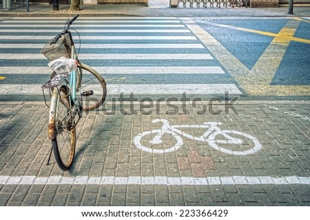 Old bicycle with bicycle symbol on bicycle parking lot at roadside in a town of China