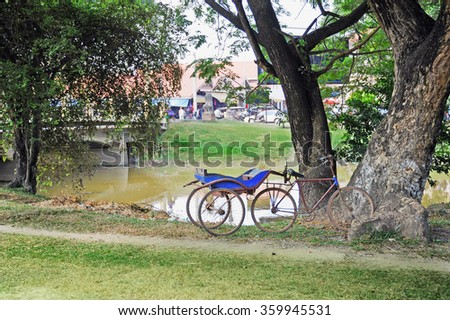 Old bicycle with trailer stay at  a large tree near the river in Cambodia