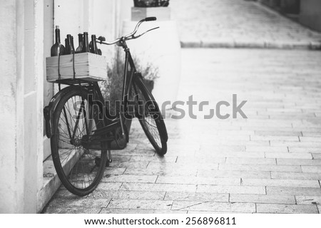 old bicycle with wooden box full of wine bottles - stock photo