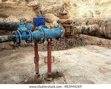 Old big drink water pipes joined with new blue gate valves and reduction joint members. Finished repaired piping waiting for covering by clay. Extreme kind of corrosion, metal corroded texture.