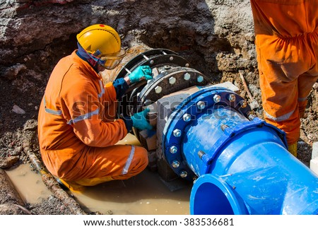 Old big drink water pipes joined with new blue valves and new blue joint members - stock photo