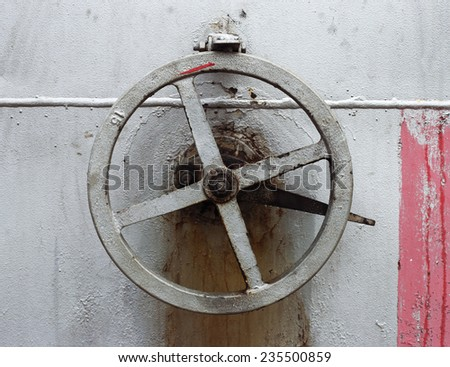 old big hand wheel on the wall of big oil tank - stock photo